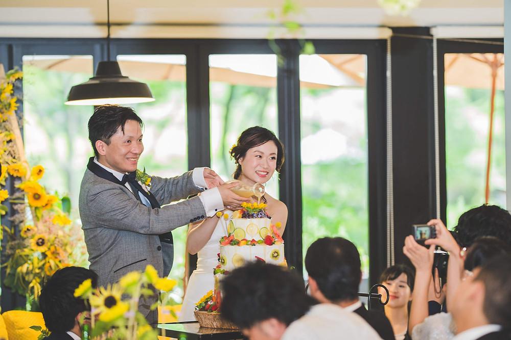日比谷パレスの結婚式でカラードリップケーキの演出をする花嫁と花婿の写真