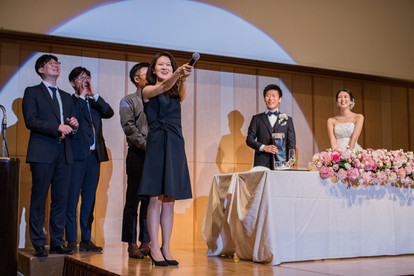 結婚式で余興をする友人と新郎新婦の写真