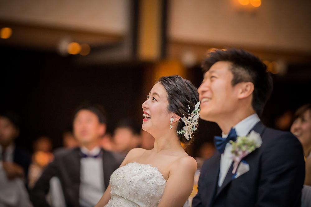 結婚披露宴で友人からのサプライズムービーを見る新郎新婦の写真