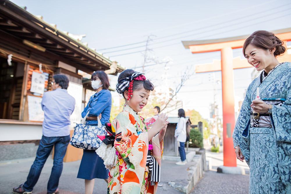 7歳の女の子が五社神社でおみくじをする七五三写真