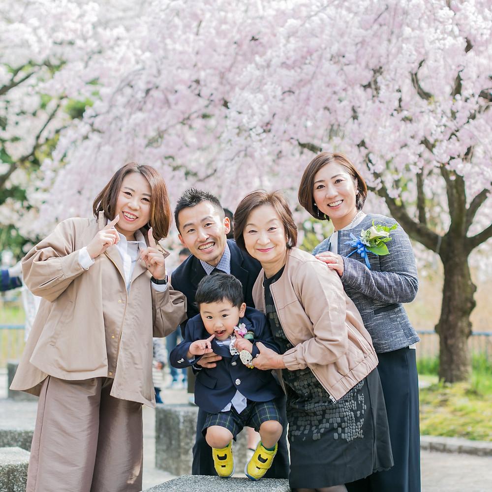 入学式で桜を背景に撮影した家族写真