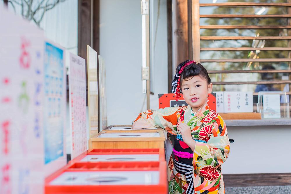 五社神社で七五三詣りをした7歳女の子がおみくじをする様子を撮影したロケーションフォト