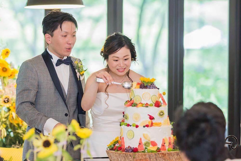 日比谷パレスの結婚披露宴でウエディングケーキの飾り付けをする新郎新婦の写真
