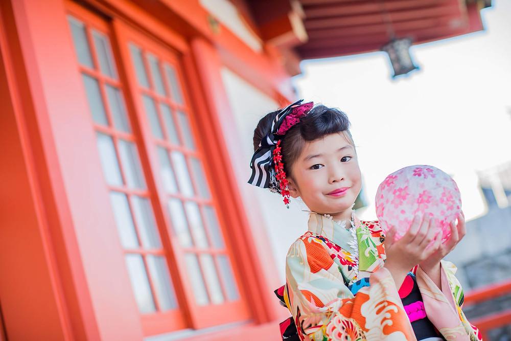 五社神社にてピンクの紙風船を使って撮影した7歳女の子の七五三ロケーションフォト