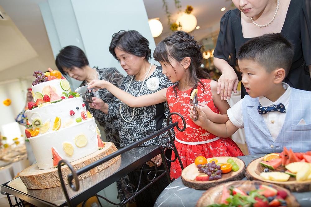 ウエディングケーキをデコレーションする子供たちを撮影した写真