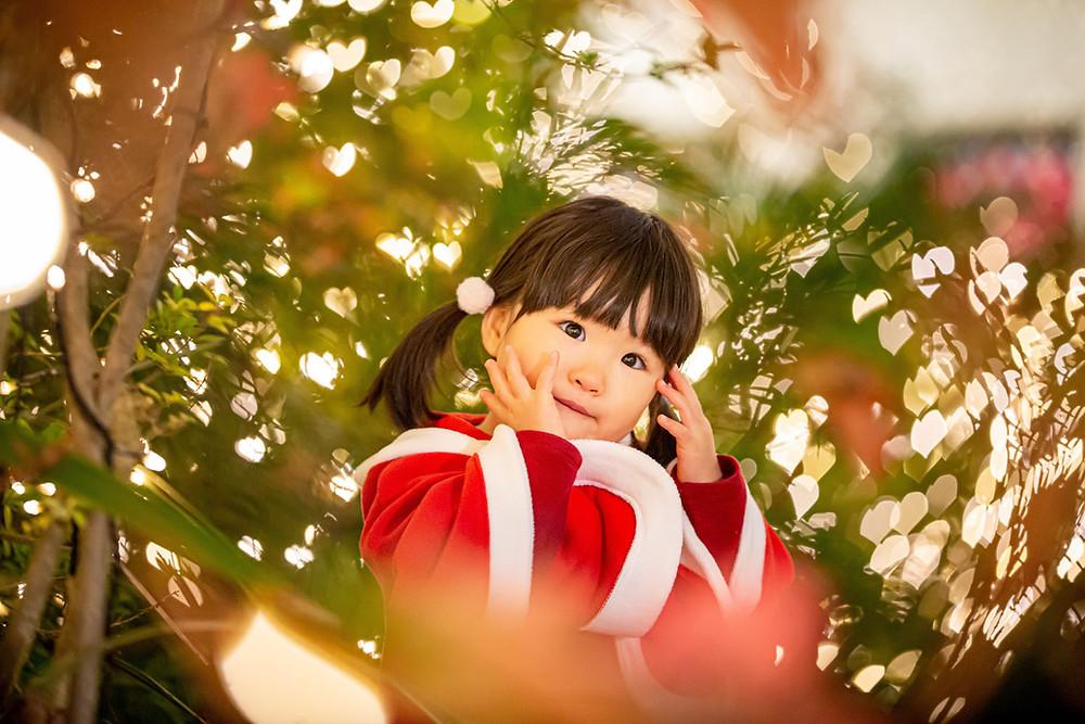 クリスマスにイルミネーションの中でサンタのコスプレをした子供を撮影した写真