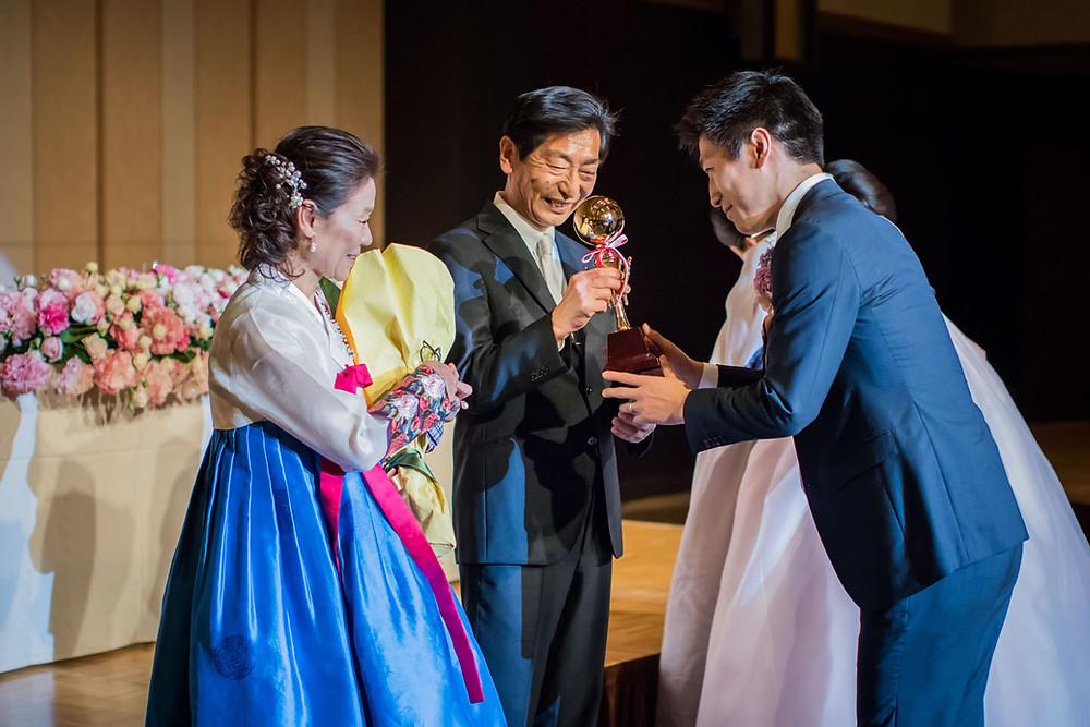 グランドプリンスホテル高輪の結婚披露宴で両親に記念品贈呈をする新郎の写真