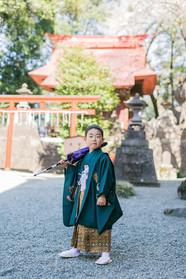 神社で和傘を持つ5歳の男の子の七五三ロケーション撮影
