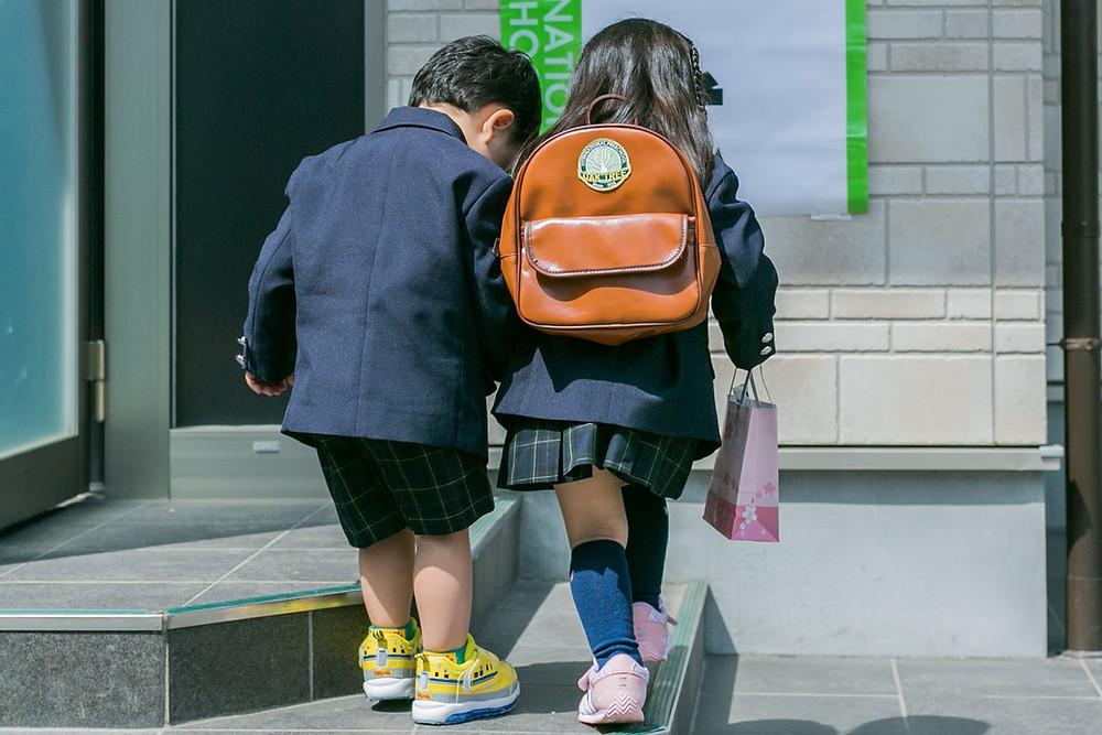 入学式で一緒に遊ぶ男の子と女の子の写真