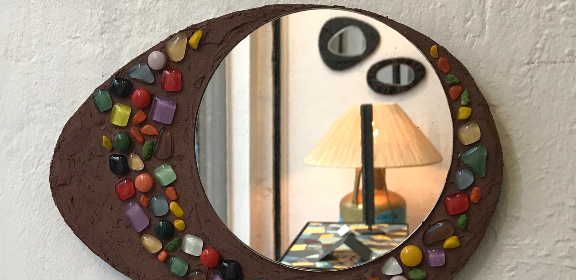 Miroir rond sur un support forme galet, jeu de mortier coloré et tesselles de verre