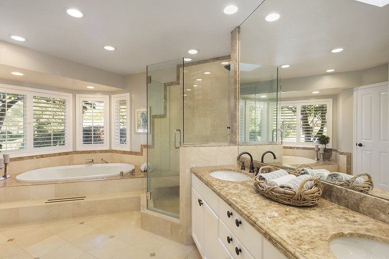 Luxury bathroom interior in marble with glass shower and oval bath tub and round shaped double sink