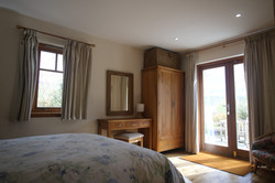 The bedroom looks out onto the secluded patio and gardens