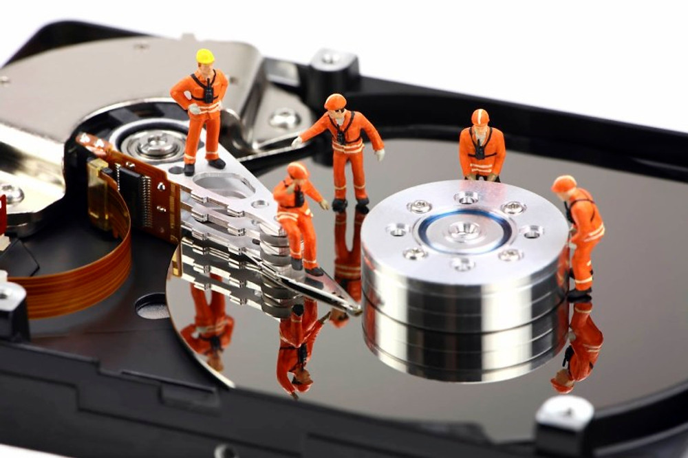 Figurines of workmen fixing a hard drive full of backups