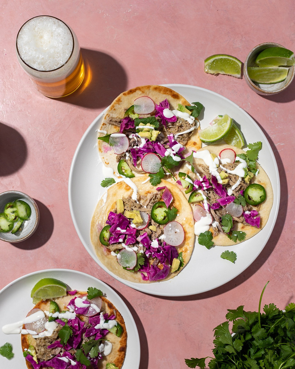 Tacos with red cabbage, cilantro, carnitas, lime juice and a little sour cream on pink background