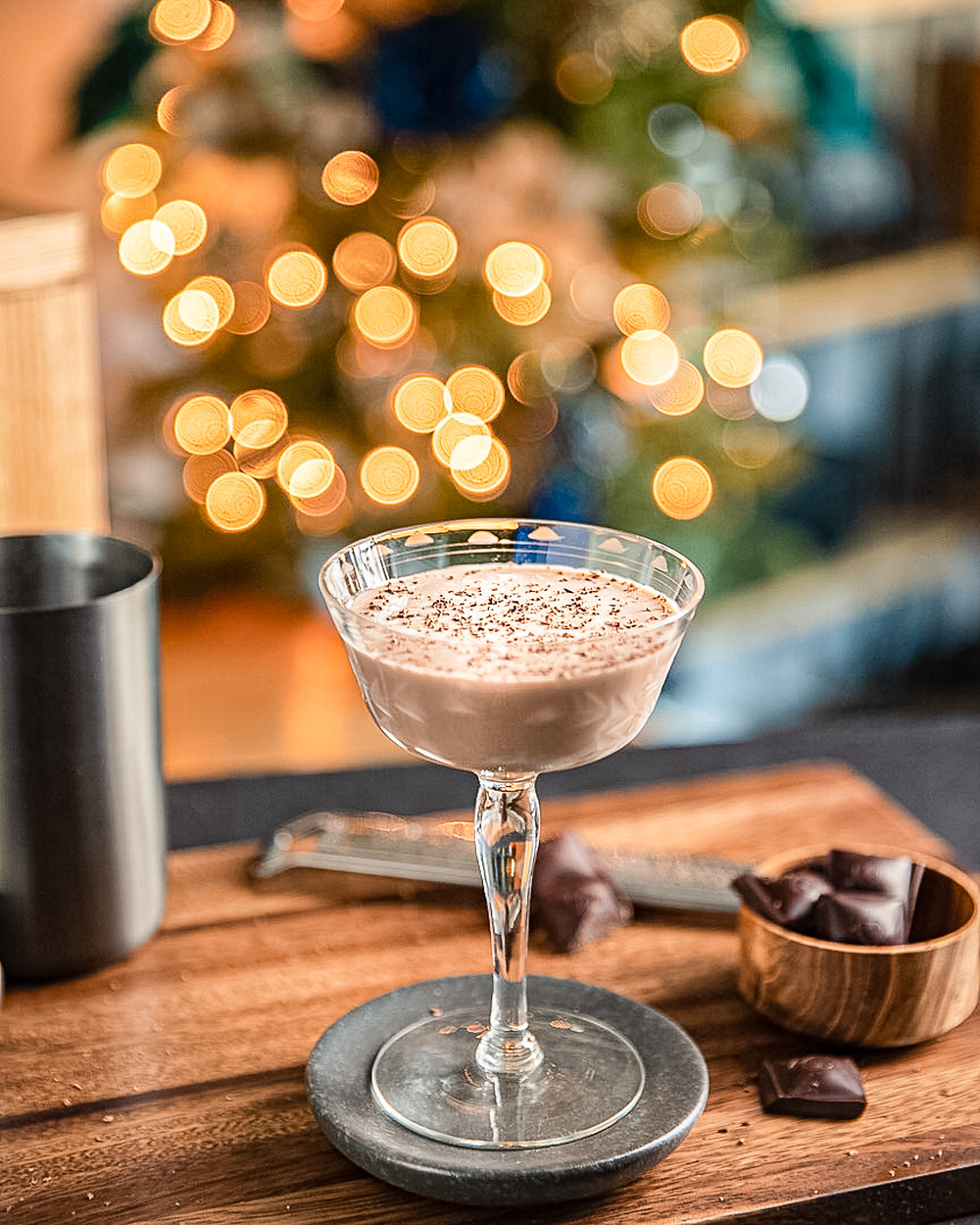 Drink photography Chocolate Amaretto Cocktail in coupe glass with chocolate shavings and christmas tree in the back