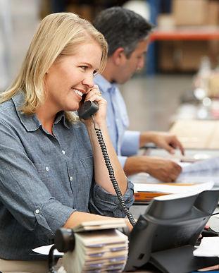 businesswoman-working-at-desk-in-warehou
