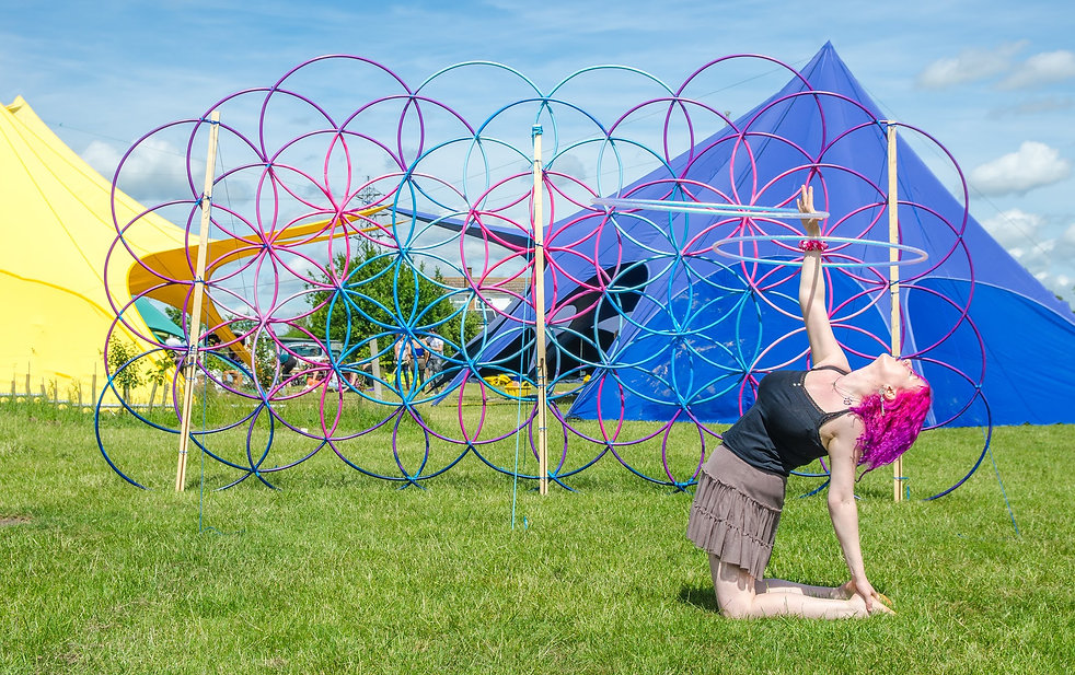 Jennie Brennen Hoop Artist performing by a hula hoop scultpure and cricus tents.