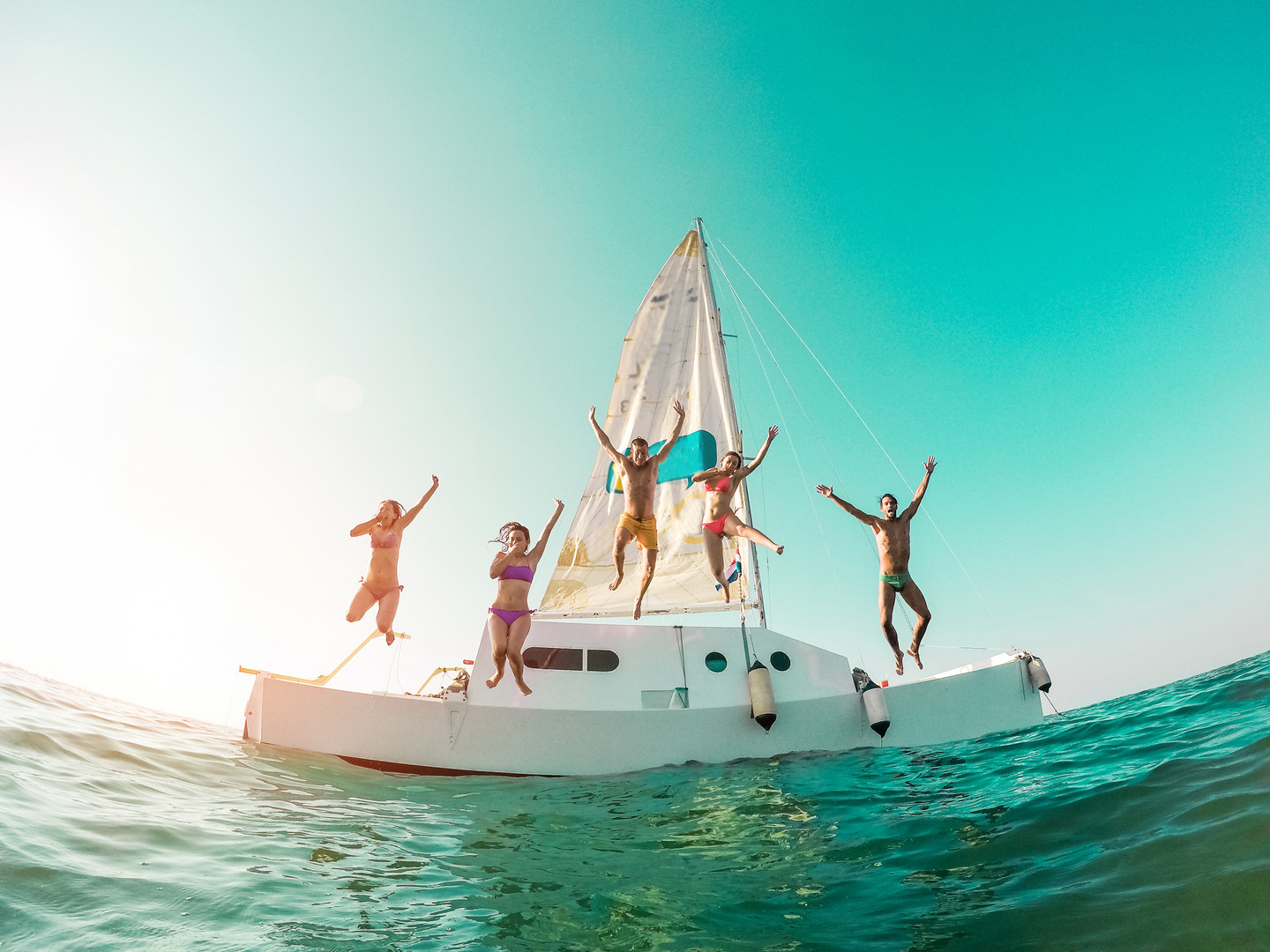 Happy crazy friends diving from sailing