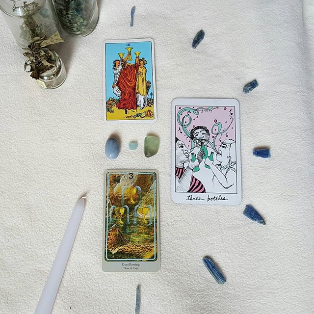 A white altar cloth background with 3 glass jars of herbs and the Rider-Waite, Collective, and Haindl 3 of water suit cards, surrounded by a half circle of blue kyanite shards, with an angelite, aquamarine, and green flourite piece amidst the cards, and a white taper candle in the corner