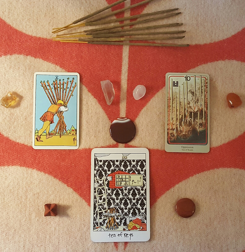 orange and cream altar cloth background with the Collective, smith rider-waite, and haindl versions of ten of wands, interspersed with red jasper, red agate, clear quartz, amber, and carnelian stones, with sticks of incense