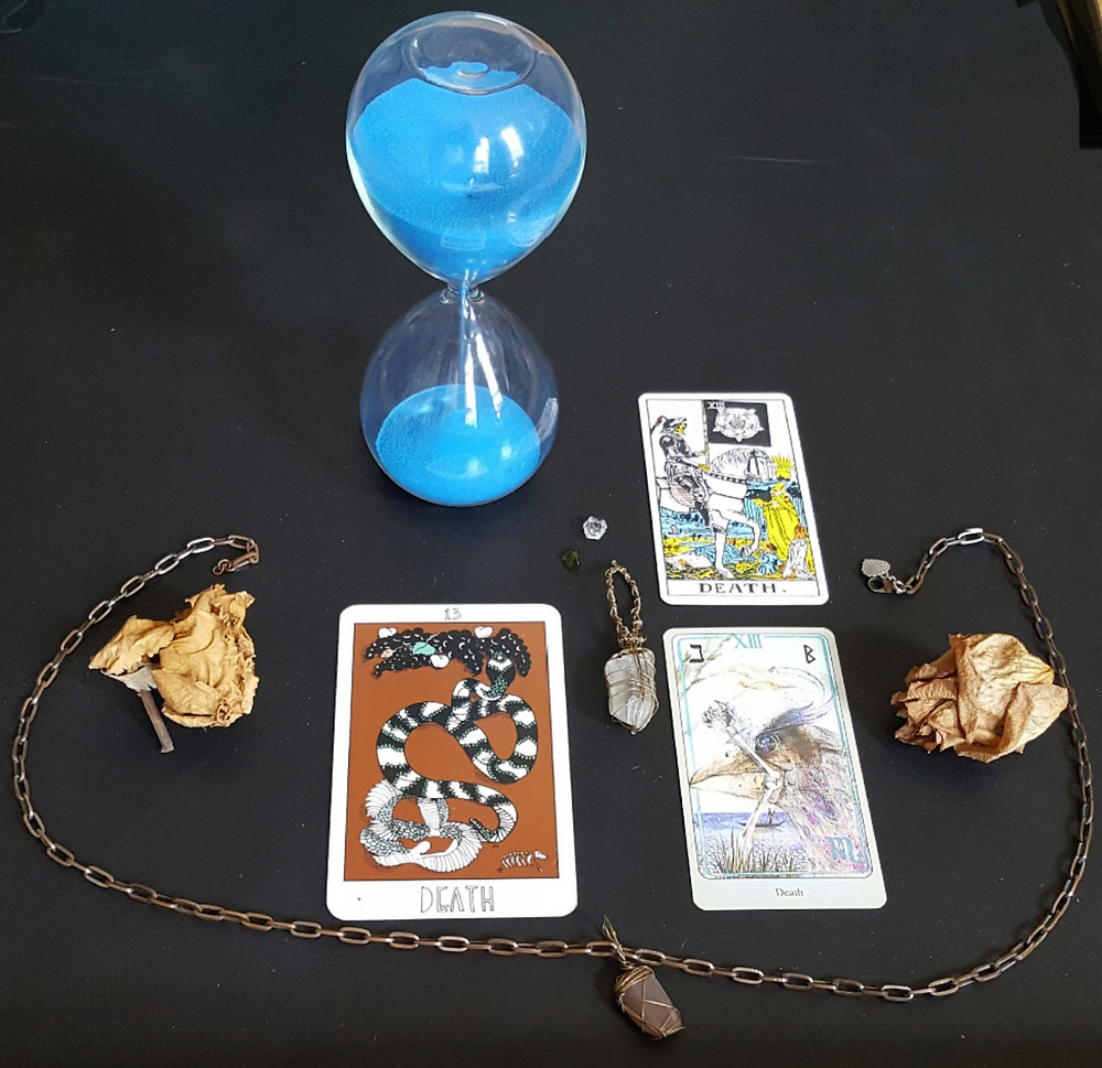 Black background with Collective tarot, haindl, and waite-smith death cards, two dead roses, a chain, a moonstone, a herkimer diamond, and a polished raw emerald