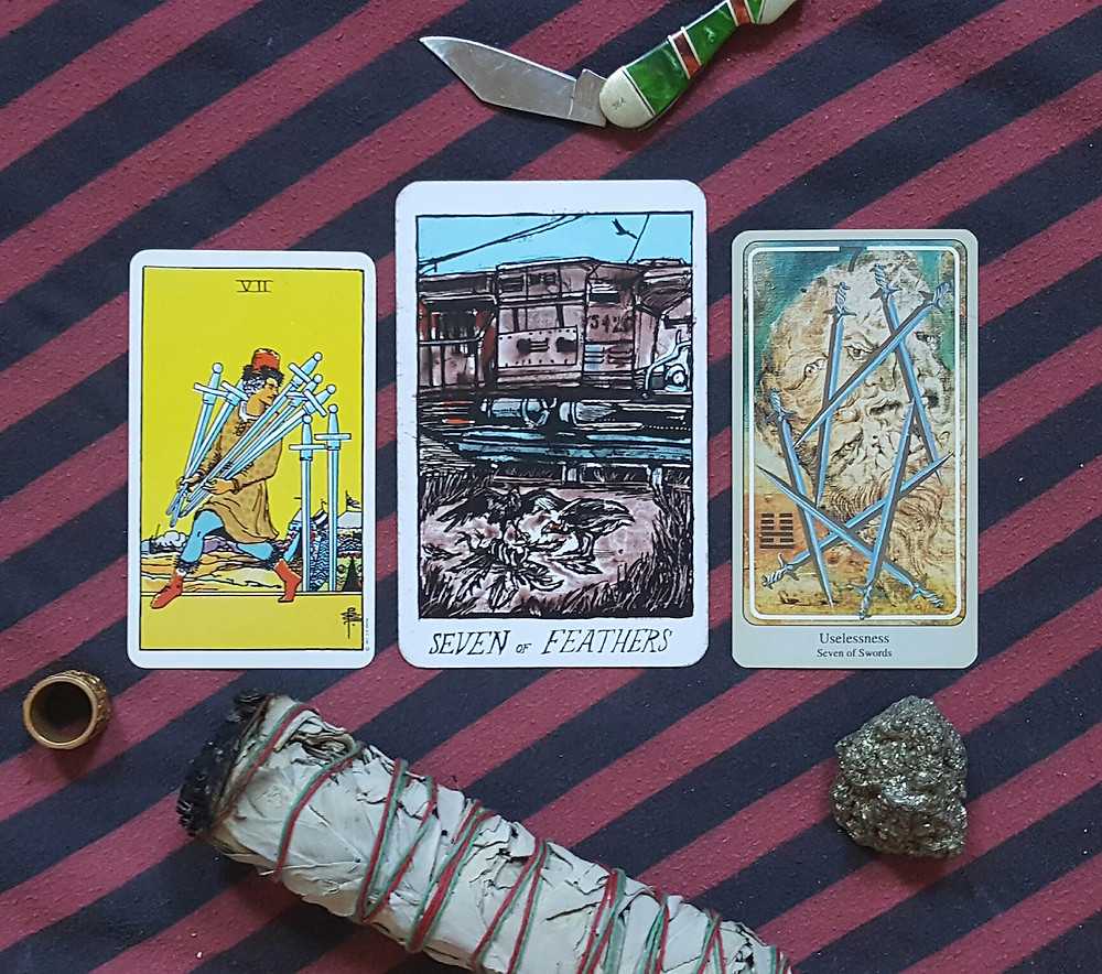 a pink and navy diagonal striped altar cloth is background to the collective tarot, haindl, and smith-rider-waite decks' versions of teh seven of swords / feathers. A pocketknife, gold ring, large smudge stick, and piece of pyrite are amidst the cards