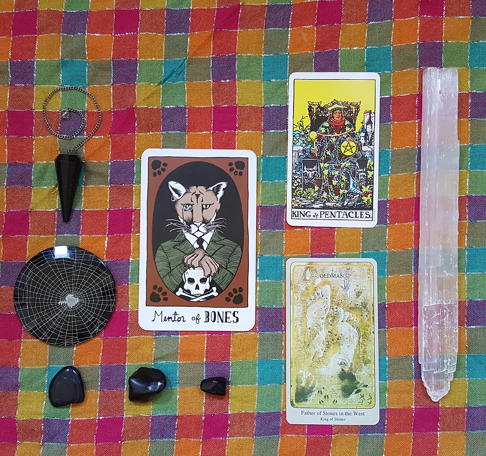 The Mentor of Bones card, the King of Pentacles card, and the Father of Stones card laid on a rainbow checkered altar cloth with three black stones and one selenite wand, a spiderweb under glass, and a black obsidian pendulum