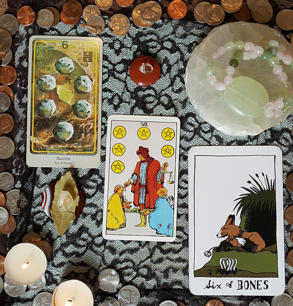 The six of stones, six of pentacles, and six of bones cards laid on a black lace altar cloth, surrounded by loose change, a pair of small candles, red jasper with a herkimer diamond, red agate with a bay leaf and citrine, and a selenite disk with a jade and rose quartz beaded bracelet