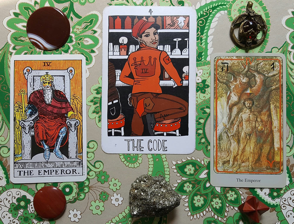 a green paisley altar cloth is background to the Rider-waite, the collective, and the haindl cards for the Emperor and the code. a red jasper disc and merkabah, a red agate disk, a piece of pyrite, and a red marble held in the talons of a bronze dragon are laid out along with the cards.