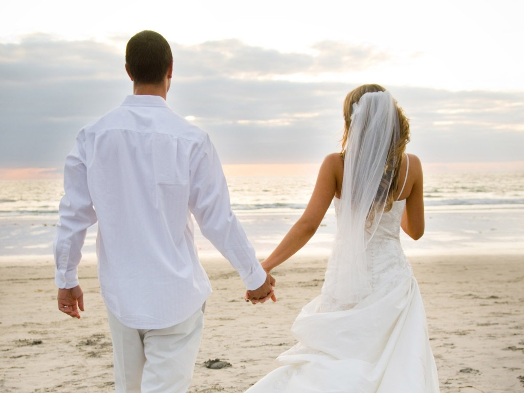 the photo of bride and groom on the beach