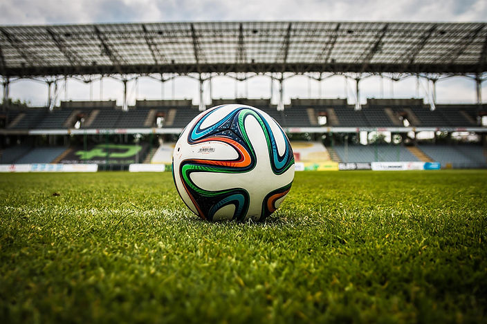 multicolored-soccer-ball-on-green-field-