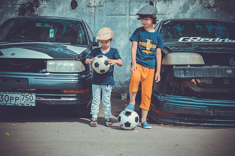 two-boys-playing-soccer-ball-beside-cars
