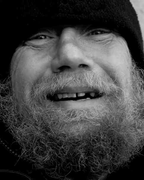 Портретное фото улыбающегося мужчины с бородой