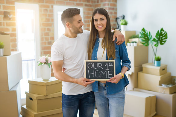 Beautiful young couple moving to a new house, smiling very happy holding blackboard with o