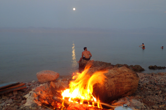 Magic moments in the evening at the beach, watching the moon near the camp fire