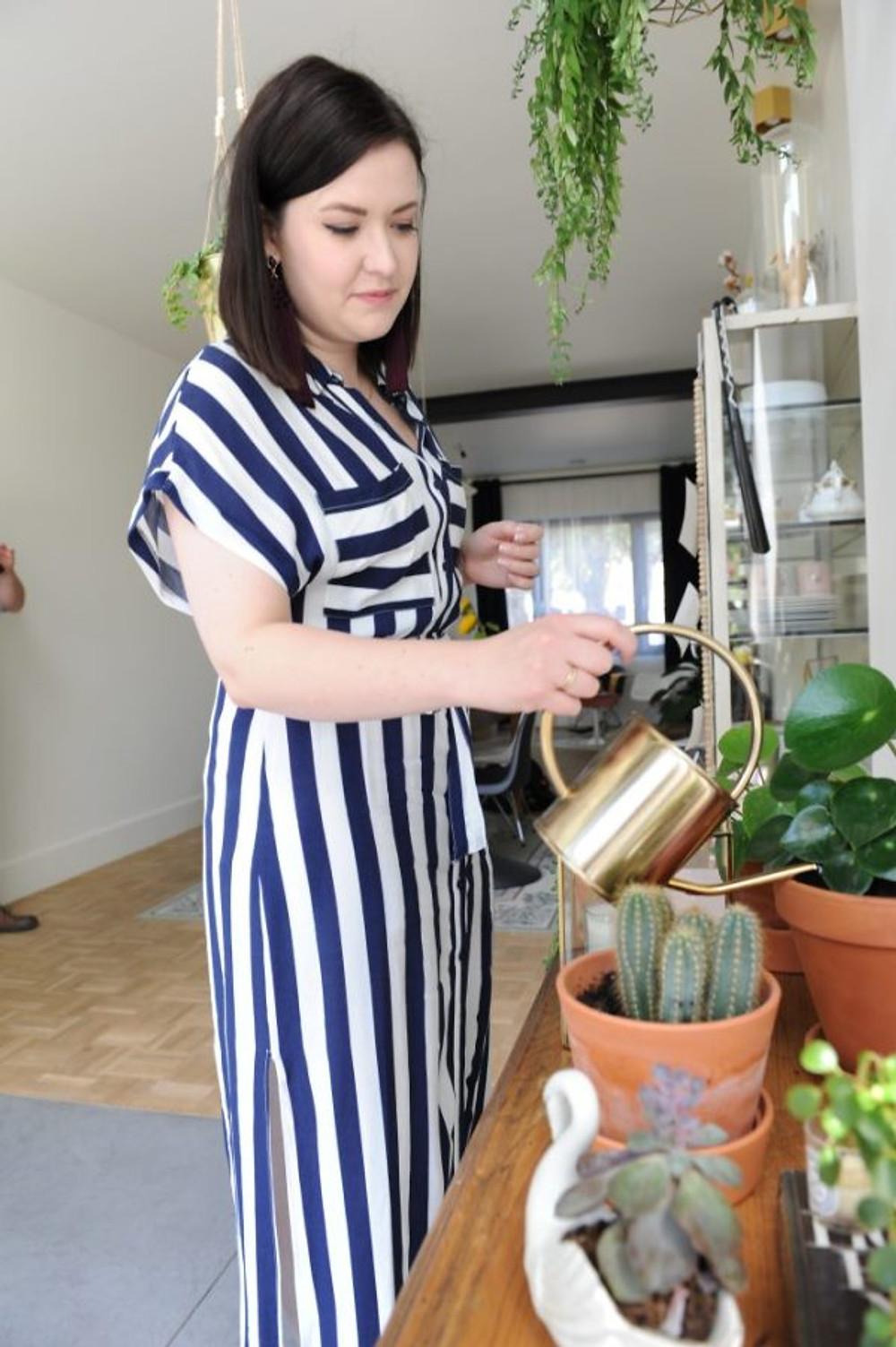 Karolien begiet haar kamerplantjes.