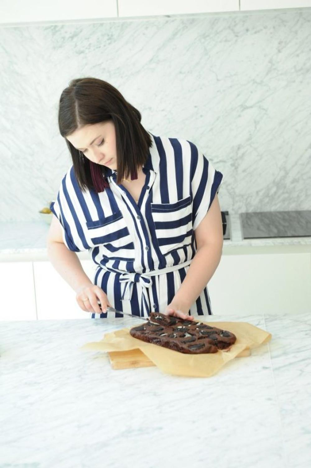 Karolien snijdt haar brownie aan in haar keuken.