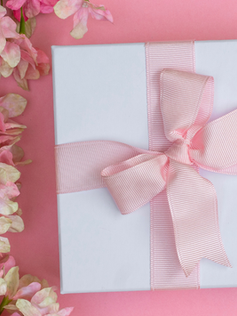 Gift Box on Pink Background with Flowers