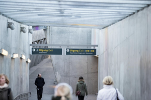 Photo of people walking in the Sisten Metro in Oslo, two exit signs can be seen