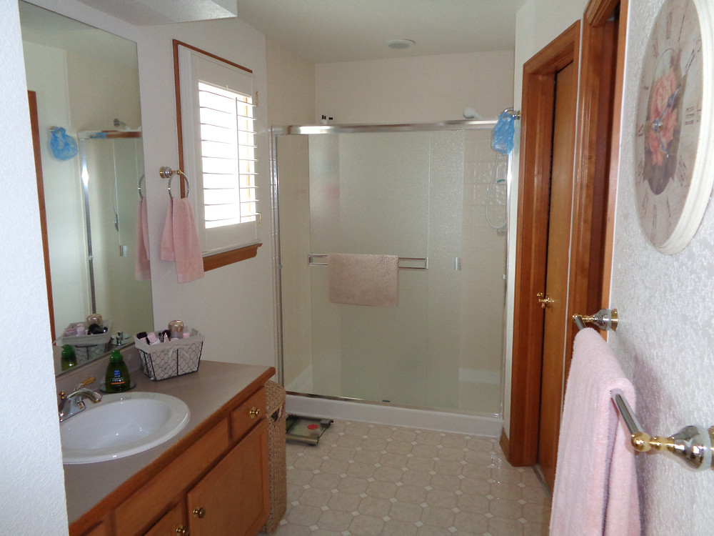 Outdated bathroom featuring standard shower and sink, pre accessible remodel