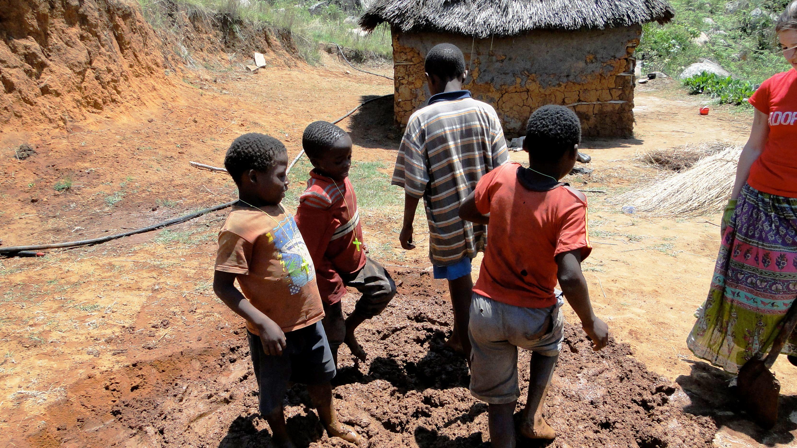 children mixing mud w/ feet for hut