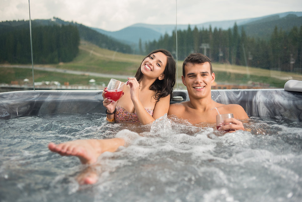Beautiful young couple enjoying a bath in Jacuzzi while drinking cocktail outdoors on roma
