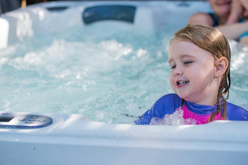 Cute girl caucasian toddler blonde hair blue eyes bright rash vest playing in water full o