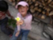 ילדה סינית מחזיקה פרח. בסין כיום מרבית הילדים הם ילדים יחידים