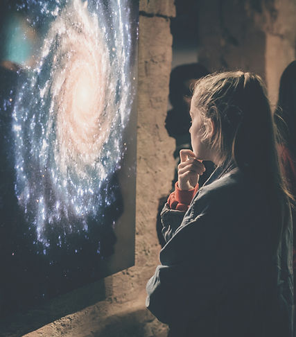 A young girl views a photograph of a spiral galaxy as part of an astrophotography installation.