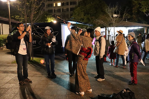 A woman in a kimono looks through a handheld telescope at a public stargazing event in Fukuoka, Japan.
