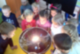 A group of Polish kindergarten children explore the solar system with an orrery.