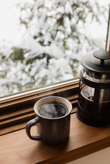 filled coffee mug and french press