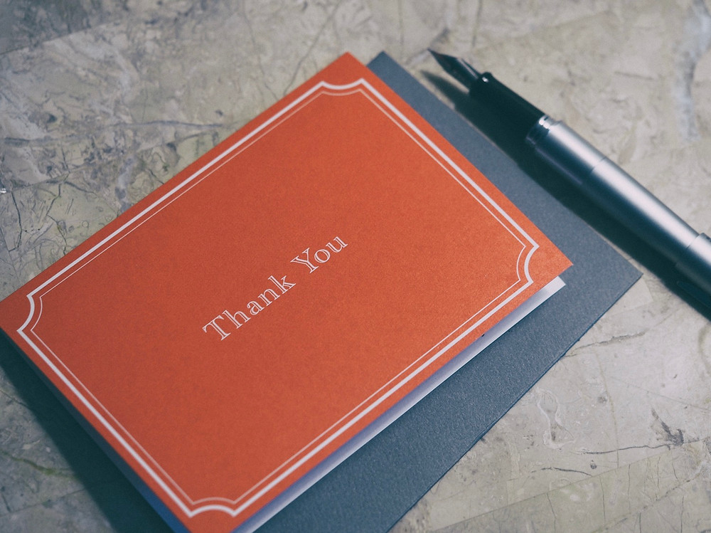 Red thank you card beside ink pen