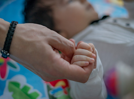 Baby holding dad's hand